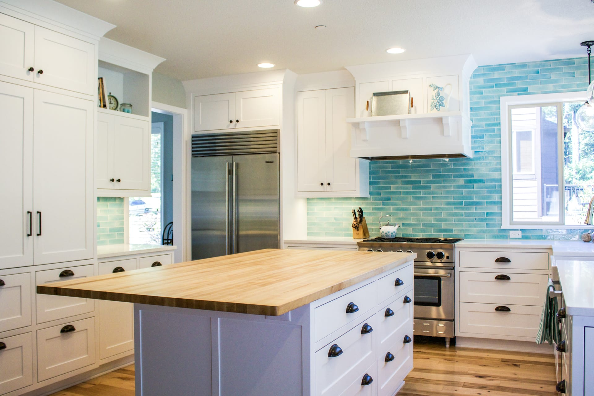 Custom designed kitchen with white cabinets and bold blue backsplash