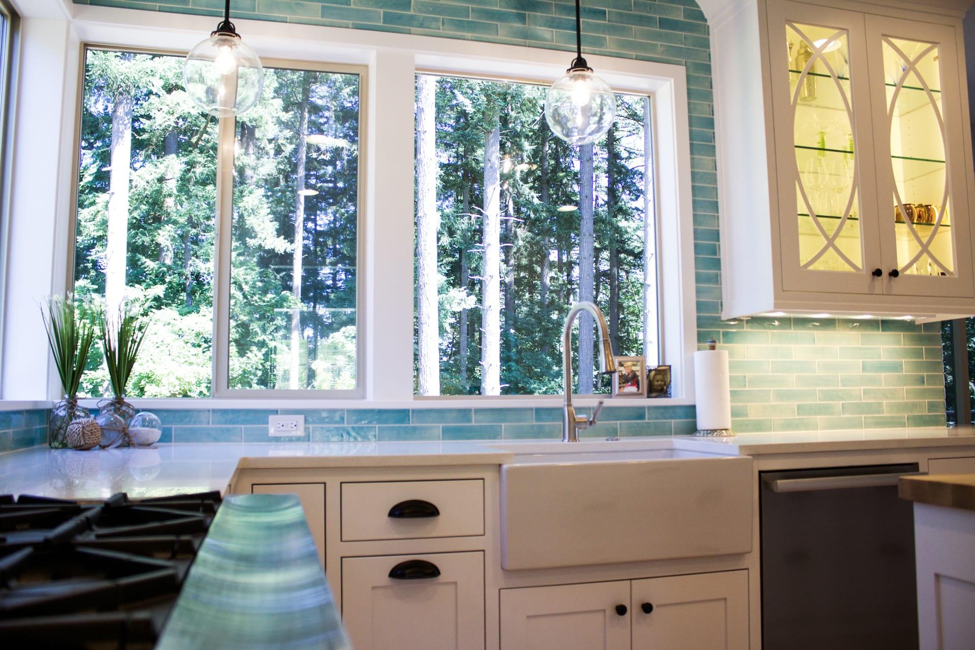 Custom designed kitchen with white cabinets and bold blue backsplash